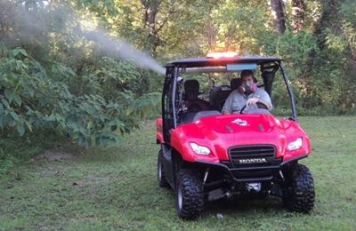 A man driving a utility vehicle spraying a chemical into a wooded area